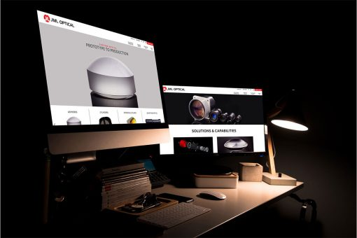 JML Optical website displayed on 2 iMacs in a dark room